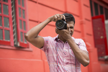 Asian Photographer shooting outside with digital camera.