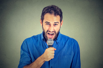 Closeup portrait frustrated man with microphone isolated on gray wall background