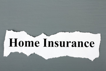 "a piece of paper with the words ""home Insurance"" on a gray wooden background"