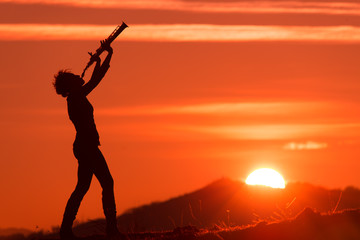 Saxophonist playing at sunset