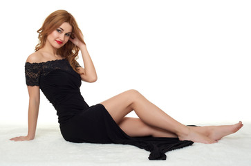 girl with bare legs lying on white fur, wearing a black dress.