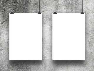 Close-up of two hanged blank frames with clips against rough concrete wall background
