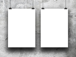 Close-up of two hanged blank frames with clips against stained wall background