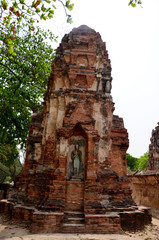 Broken buddha statue and ancient building