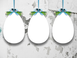 Close-up of three hanged Easter egg blank frames with aqua ribbons against concrete wall