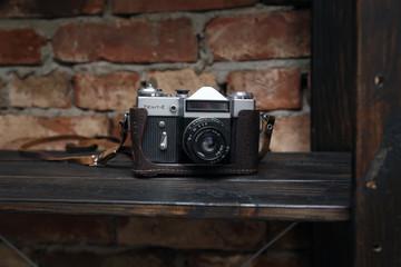 Старый раритетный фотоаппарат лежит на деревянной коричневой книжной полке
