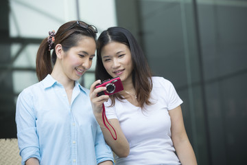 Two happy Asian women taking photos with a DSLR camera.