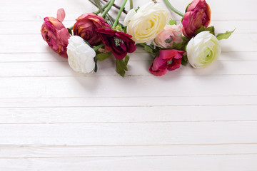 Border from  white and pink flowers  on white wooden background.