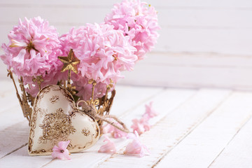 Pink  hyacinths and decorative heart on white  painted wooden pl