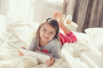 Cute little girl working with tablet computer lying in bed