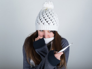 young woman in a knitted hat and scarf, holding hands in the thermometer. she seems sick