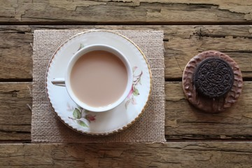 Traditional milky tea served in a bone china cup and saucer with two chocolate cookies on a rough wooden background