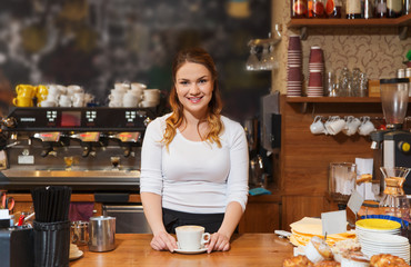 happy barista woman with latte at coffee shop