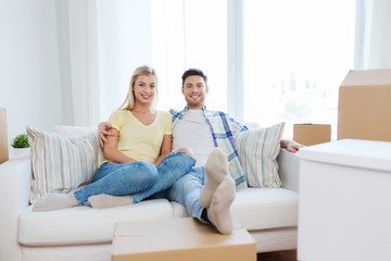 happy couple with big cardboard boxes at new home