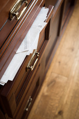 A drawer of wooden commode  full of paper documents. Selective focus