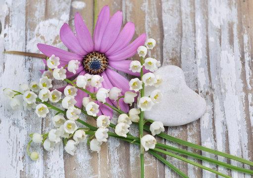 bouquet de muguets et cœur  en pierre sur table bois blanc