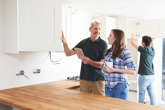 Woman With Carpenter Looking At Plans For Kitchen On Digital Tab