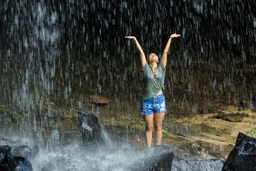 Woman freedom under waterfall