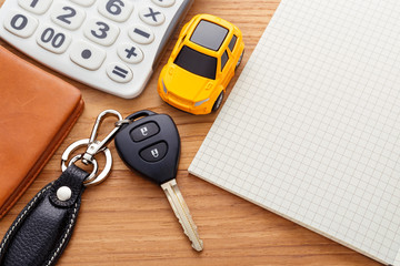 Car key with notebook calculator and pocket money on wood table