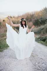 portrait of bohemian bride in nature, with white dress and crown