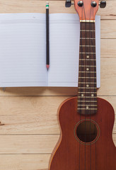 blank notebook with pencil and ukulele on wooden table