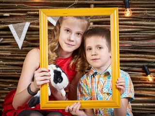 Girl and boy with rabbit in frame of picture