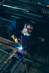 Man in workplace welding metal