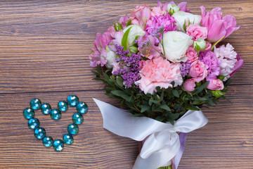 Valentine flowers with heartshaped jewellery on wood