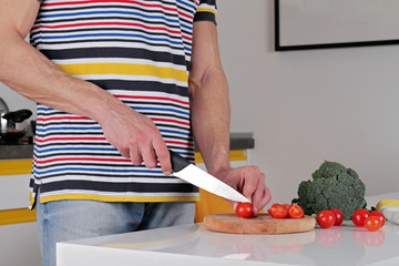Man cutting tomato, making salad. Cooking at home. Healthy lifestyle, diet food