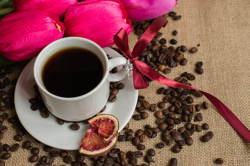 Coffee cup with raw beans on burlap with pink tulips