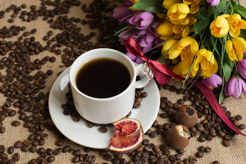 Coffee cup with raw beans on burlap with flower