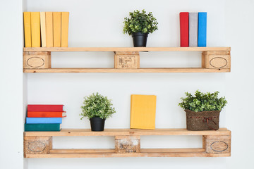 Books and flowers on wooden shelf