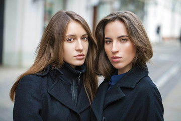 Close Up portrait of two friends in a black coat