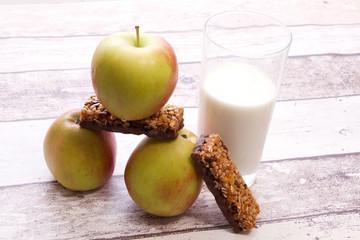 Stapel Äpfel mit Vollkornriegel und Glas Milch