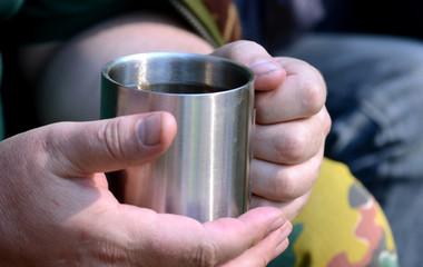 man holding a metal cup closeup