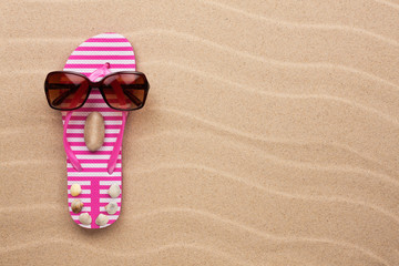 Concept of a woman's face, flip-flops and sunglasses