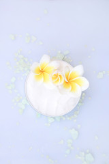 Top view of organic cream with frangipani flower