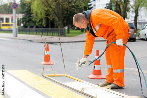Road painter man worker marking street lines zebra crossing