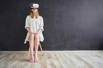The girl in white sitting on a chair in the virtual reality helmet