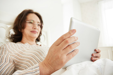 Attentive and cheerful mature woman using a tablet pc lying on her bed in a bedroom.