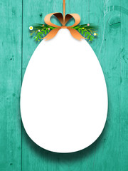 Close-up of one hanged decorated Easter egg blank frame with ribbon against aqua wooden background