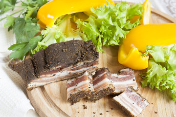 A delicious smoked ribs with spices around fresh yellow pepper lettuce leaves parsley on wooden board and napkin background