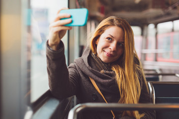 Young woman taking selfie in a tramway