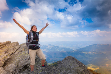 Young happy woman with backpack standing on top of the mountain.