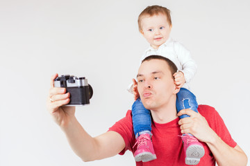 Funny father and child making selfie at vintage camera