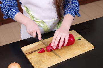 Little girl is cutting vegetables for salad closeup