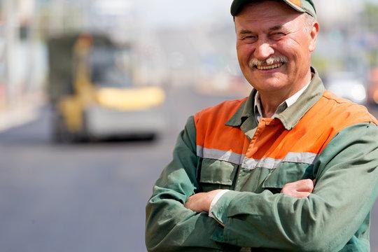 Portrait positive happy Road Worker on Asphalt Roller Machine background