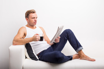 Man relaxing on couch with coffee mug and reading newspaper
