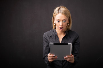 Woman looking at tablet in shock