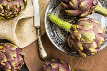 Fresh purple artichokes in oriental bowl closeup background